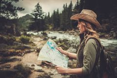 Woman hiker, searching right direction on map near wild mountain river. Stock Images