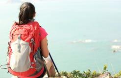 Woman hiker sit on seaside rock Royalty Free Stock Image