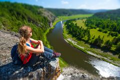 Woman hiker sits on the rock. And enjoys the river flowing in the valley. Ural Mountains and the River of Belaya, Russia royalty free stock photos