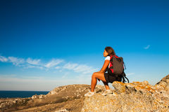 Woman hiker sits on seaside mountain rock Stock Photos
