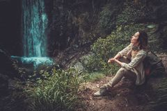 Woman hiker sitting near waterfall in deep forest. Stock Photo
