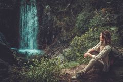 Woman hiker sitting near waterfall in deep forest. Royalty Free Stock Photography