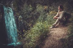 Woman hiker sitting near waterfall in deep forest. Stock Images