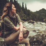 Woman hiker sitting on the stone near wild mountain river. Stock Photo