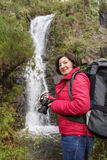 Woman hiker smiling and photographed waterfall. Stock Photos