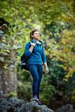 Woman hiker smiling standing outside in forest Stock Photo