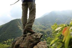 Woman hiker stand on mountain peak rock Stock Photos