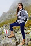 Woman hiker standing on the mountain rocks Royalty Free Stock Photos