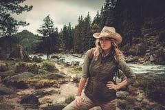 Woman hiker standing near wild mountain river. Stock Photography