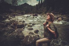 Woman hiker standing near wild mountain river. Stock Photo