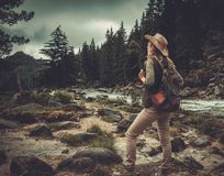 Woman hiker standing near wild mountain river. Stock Images