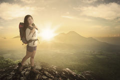 Woman hiker standing with sunset and mountain Royalty Free Stock Photo