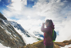 Woman hiker standing on the top of mountain and looking in binoc. Ulars outdoor Royalty Free Stock Photography