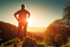 Woman hiker stands on the hill. And looks into valley filled with sunrise light stock photo