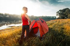 Woman hiker. Stands near the tent set on a coast of a river and looks at camera stock photography