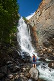 Woman hiker stands on the rock. Barefoot and enjoys waterfall view. Altai, Russia royalty free stock images