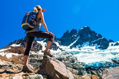 Woman hiker stands on the rocks stock image