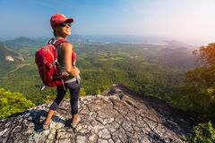 Woman hiker stands on top of the mountain. And smiles and looks into camera stock image