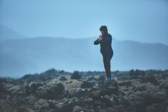 Woman hiker stands in yoga pose on volcanic Lava fields on background of mountains of Iceland. Stock Image