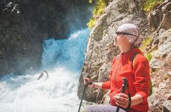 Woman hiker with sticks near waterfall. Tourism concept Stock Images