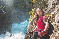 Woman hiker with sticks near waterfall. Tourism concept Stock Image