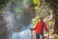 Woman hiker with sticks standing near waterfall. Tourism concept Stock Photos