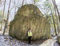 Woman hiker stops beside huge boulder to marvel at wilderness en Royalty Free Stock Images
