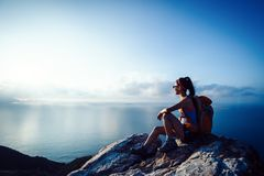 Woman hiker at sunrise seaside royalty free stock photography