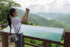 Woman hiker taking photo with camera at mountain Stock Images