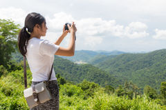 Woman hiker taking photo with camera at mountain Royalty Free Stock Photo