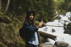 Woman hiker taking photo with cell phone at forest in tibet,china royalty free stock photo