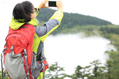 Woman hiker taking photo with cell phone Stock Images