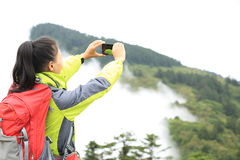 Woman hiker taking photo with cell phone Stock Photo