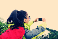 Woman hiker taking photo with cell phone Royalty Free Stock Image