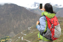 Woman hiker taking photo with cell phone Royalty Free Stock Images