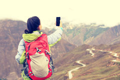 Woman hiker taking photo with cell phone Royalty Free Stock Photography