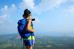 Woman hiker taking photo with cellphone hiking on mountain peak Stock Photo