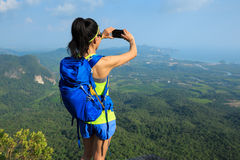 Woman hiker taking photo with cellphone hiking on mountain peak Royalty Free Stock Image