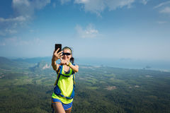 Woman hiker taking photo with cellphone hiking on mountain peak Stock Images