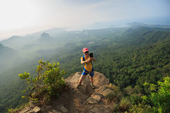 Woman hiker taking photo with cellphone hiking on mountain peak Royalty Free Stock Photo