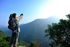 Woman hiker taking photo Stock Photo