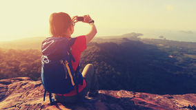 Woman hiker taking photo with cellphone on mountain top Stock Image