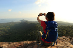 Woman hiker taking photo with cellphone on mountain top Royalty Free Stock Photo