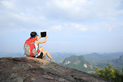 Woman hiker taking photo with digital tablet on mountain peak Royalty Free Stock Image