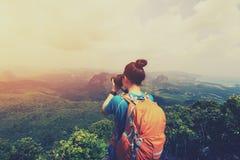 Woman hiker taking photo on mountain peak Stock Photography