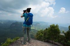 Woman hiker taking photo on mountain peak Royalty Free Stock Images