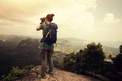 Woman hiker taking photo on mountain peak Stock Photos