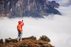 Woman hiker taking photo with smart phone on mountain peak Stock Photo