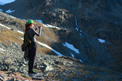Woman hiker taking photo with smart phone Stock Photos