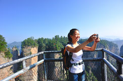 Woman hiker taking photo Stock Images